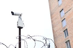 Camera video surveillance on the building background mounted on a brick wall, fenced with barbed wire. Stock Photography