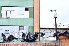 Camera video surveillance on the building background mounted on a brick wall, fenced with barbed wire. Stock Images