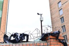 Camera video surveillance on the building background mounted on a brick wall, fenced with barbed wire. Stock Image