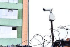 Camera video surveillance on the building background mounted on a brick wall, fenced with barbed wire. Royalty Free Stock Photo
