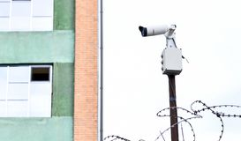 Camera video surveillance on the building background mounted on a brick wall, fenced with barbed wire. Royalty Free Stock Image