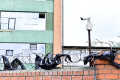 Camera video surveillance on the building background mounted on a brick wall, fenced with barbed wire. Stock Photos