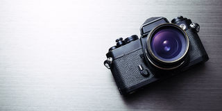 Camera. Vintage camera on brushed aluminum texture background royalty free stock images