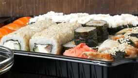 Camera zooms. Large sushi set with a variety of sushi rolls as well as maki, nigiri, gunkan on a stylish black wooden. Camera zooms. A large sushi set with a stock video