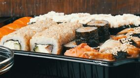 Camera zooms. Large sushi set with a variety of sushi rolls as well as maki, nigiri, gunkan on a stylish black wooden. Camera zooms. A large sushi set with a stock video footage
