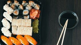 Camera zooms. Stylishly laid sushi set on a black wooden background next to soy sauce and Chinese bamboo sticks. Various. Camera zooms. Stylishly laid sushi set stock video
