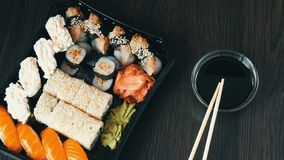 Camera zooms. Stylishly laid sushi set on a black wooden background next to soy sauce and Chinese bamboo sticks. Various. Camera zooms. Stylishly laid sushi set stock footage