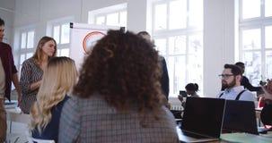 Camerabewegingen rond gelukkige multi-etnische collega's die, actieve bespreking bij modern bureau bedrijfsseminarie samenwerken stock video