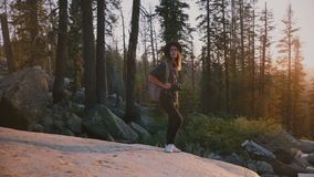 Camerabewegingen rond opgewekte toeristenmeisje status op grote rots in diep hout van Yosemite op ongelooflijke zonsondergang lan stock footage