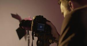 Cameraman/équipe de tournage employant l'appareil-photo de DSLR dans l'ensemble de studio de film banque de vidéos