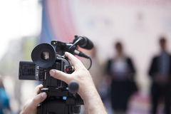 Cameraman. Covering an event with a video camera Royalty Free Stock Images