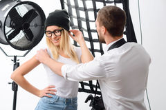 Cameraman adjusts posture of young model. Picking right pose. Male photographer helps young appealing model to adjust with necessary pose royalty free stock photo