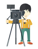 Cameraman. An asian cameraman looking through movie camera on a tripod vector flat design illustration on white background. Vertical layout stock illustration