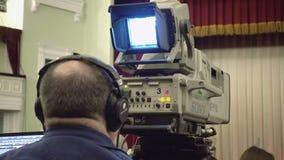 Cameraman with a big TV broadcast camera. Kiev, Ukraine - January 11, 2017: Cameraman is preparing to shoot stage performance with a big TV broadcast camera stock footage