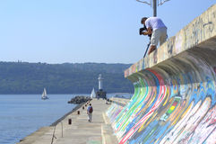 Cameraman on breakwater Stock Photos