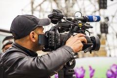 Cameraman con su tirar de la cámara de vídeo al aire libre en la ciudad imagen de archivo libre de regalías