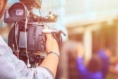 Cameraman die professionele digitale videocamera met behulp van Openlucht opstelling royalty-vrije stock fotografie
