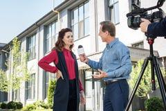 cameraman en mannelijke nieuwsverslaggever die succesvolle onderneemster interviewen royalty-vrije stock foto's