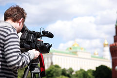 Cameraman filming. Man with HD camcorder on tripod, selective focus stock image