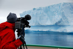 Cameraman filming in antarctica. Cameraman filming in an icy natural environment, with iceberg Royalty Free Stock Image