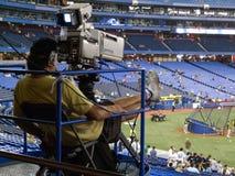 Cameraman filming a baseball match Stock Photography