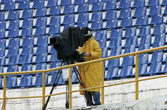 A cameraman filming a football game on a stadium. In the rain Royalty Free Stock Photography