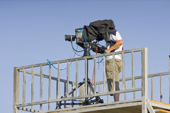 A cameraman filming a football game on a stadium. Profiled in a blue sky Royalty Free Stock Images