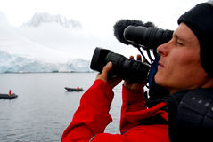 Cameraman filming an iceberg. Cameraman filming in an icy natural environment Royalty Free Stock Images