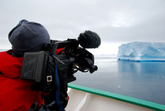 Cameraman filming an iceberg. Cameraman with large video camera Stock Image
