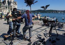 A cameraman films a scene for a Turkish soap opera in Istanbul in Turkey. A cameraman films a scene of a man feeding the pigeons adjacent to the Bosphorus at Stock Photo