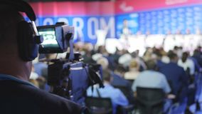 The cameraman makes a direct broadcast of the event and events for businessmen and politicians. Cameraman with camera on. Stage at concert. Broadcasting stock footage