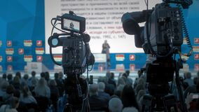 The cameraman makes video for television. Auditorium, seminar and lecture on business. Professional ideas, politics or