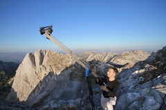 Cameraman on mountain. Camera man with camera on crane on Mountain peak Royalty Free Stock Photography
