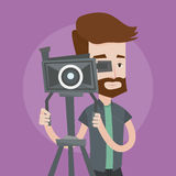 Cameraman with movie camera on tripod. A hipster cameraman with the beard looking through movie camera on a tripod. Young man with professional video camera. A stock illustration