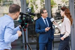 cameraman and news reporter with microphone interviewing businessman near office