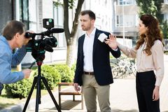 cameraman and professional news reporter with businessman royalty free stock photography