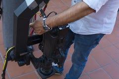 Cameraman que comprueba el equipo de la cámara en la televisión de difusión foto de archivo