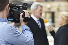 Cameraman Recording Female Journalist Interviewing Businessman. In Street Stock Image