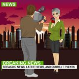 Cameraman recording female journalist or TV reporter presenting the news in front of night city with skyscrapers. Back view of cameraman recording female Stock Photography