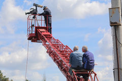 Cameraman on red telescopic lift with two worker. Cameraman on telescopic lift with two worker Royalty Free Stock Photos