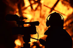 Cameraman reporter journalist filming building on fire flames