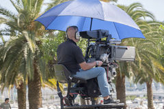 Cameraman. Shelters from the sun with an umbrella during a shoot Royalty Free Stock Photography