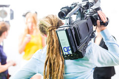 Cameraman shooting with camera on film set Stock Photos