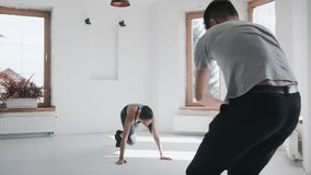 Cameraman shooting fit girl in sportswear running plank on floor. Backstage stock footage