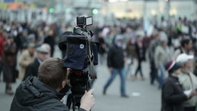 Cameraman shoots people at a crowded place. Shot on Canon 5D Mark II with Prime L Lenses