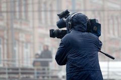The cameraman shoots a television report in the rain on the street Royalty Free Stock Image