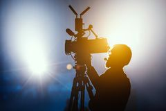 Free Cameraman Silhouette On A Live Studio News Stage.Professional Cameraman With Headphones In Television News Broadcast Stock Photography - 137820162
