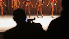 Cameraman silhouette recording video of beauty contest, models posing on stage