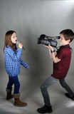 Cameraman and singer. Little cameraman films a singing girl royalty free stock image