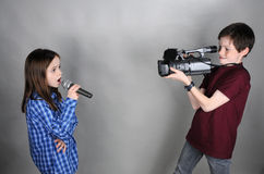 Cameraman and singer. Little cameraman films a singing girl Royalty Free Stock Images